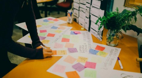 person writing on coloured sticky notes