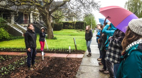 Farmer Elana talking about City Beet Farm with a group of workshop participants with umbrellas in the rain.